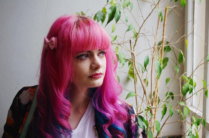 Ich stehe in einem Treppenhaus, schaue aus dem Fenster, schräg hinter mir eine Pflanze mit grünen Blättern.