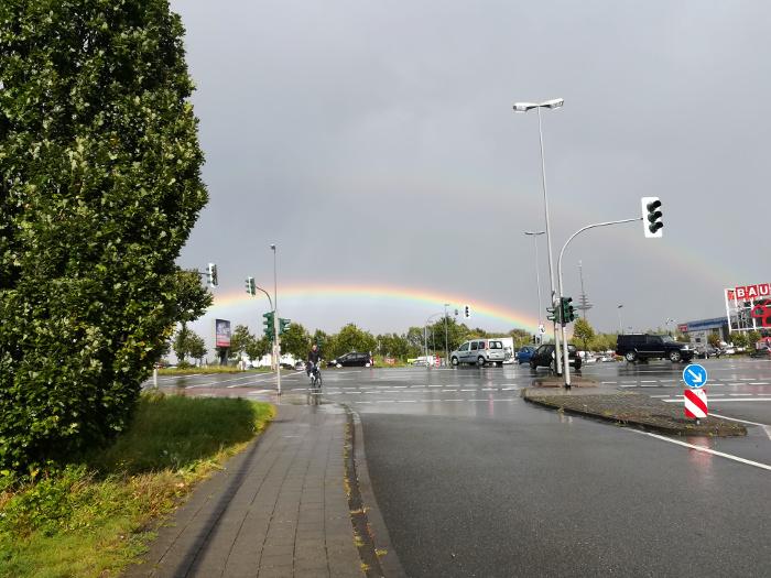Regebogen über einer regennassen Straße nach Gewitter