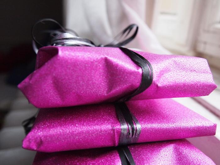 Drei aufeinander getürmte Geschenke auf dem Fensterbrett, eingewickelt in pink glitzerndes Papier.