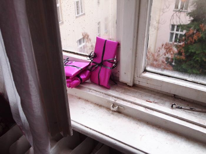 Pink verpackte Geschenke stehen auf dem Fensterbrett, draußen ein Tannenbaum.