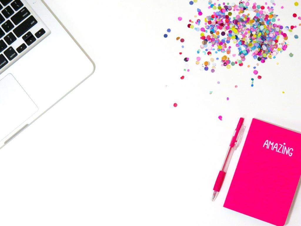 """Buntes Konfetti neben einem Laptop und einem pinkfarbenen Notizbuch mit der Aufschrift """"Amazing"""""""