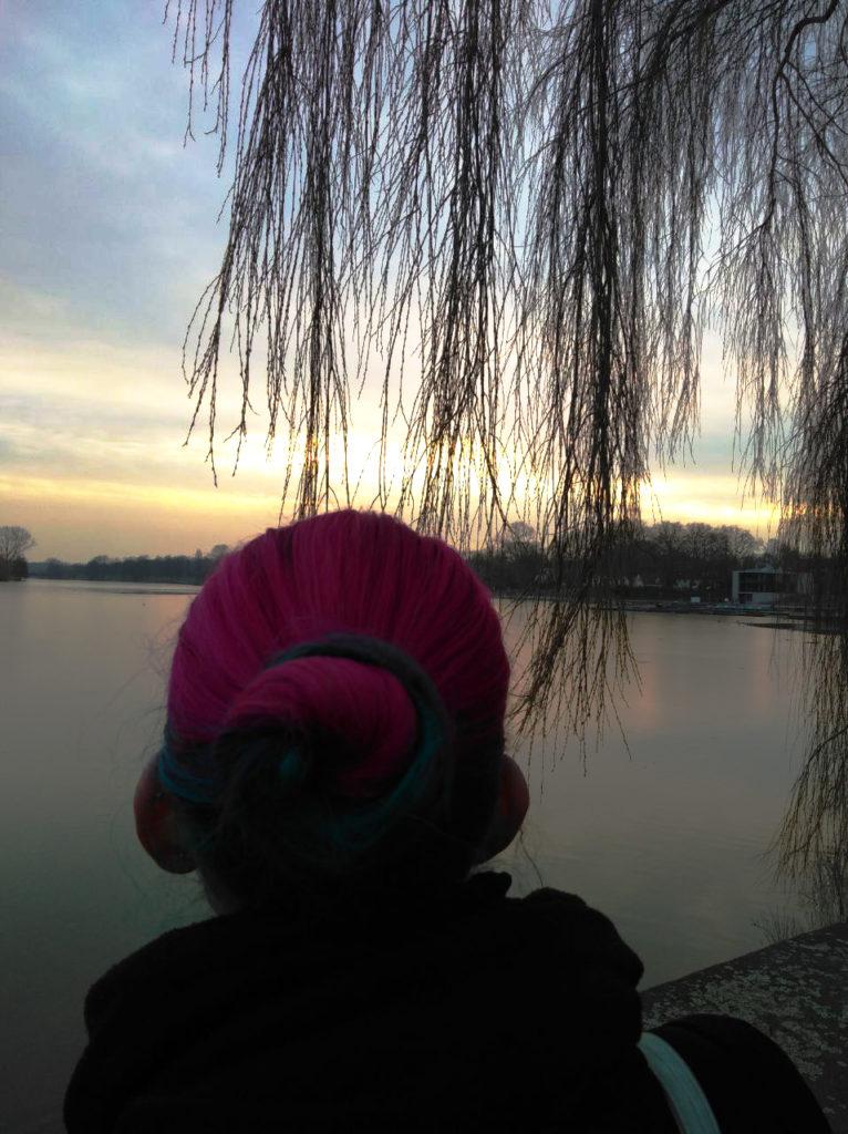 Ich an einem See, während die Sonne untergeht, über mir eine Trauerweide.