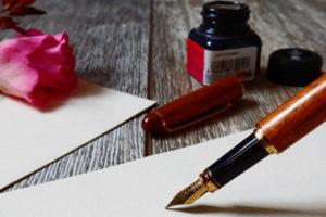 Füller, Papier, Tintenfass und rosa Rose.