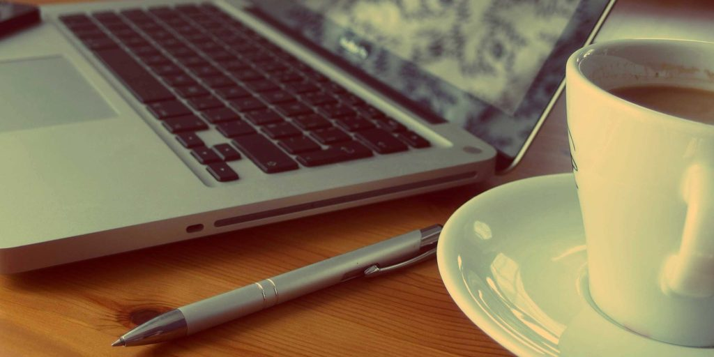 Laptop, Stift und Kaffeetasse