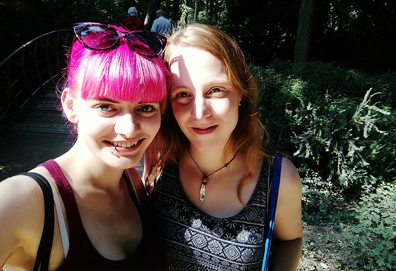 Anna und Lucia lächelnd im Tiergarten (Park) bei sonnigem Wetter.