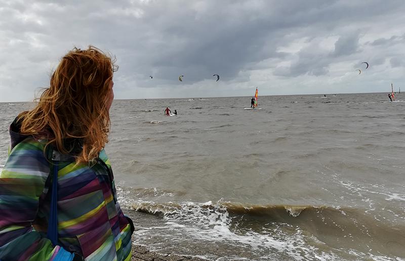 Anna steht mit dem Rücken zur Kamera am Meer und beobachtet Surfer.