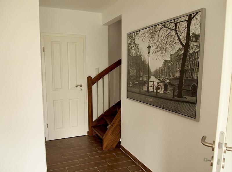 Flur unserer Ferienwohnung mit einer Treppe am Ende und einem Bild an der Wand, das Amsterdam zeigt.