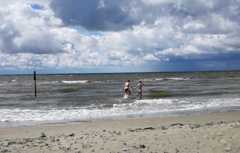 Anna und Lucia rennen Hand in Hand ins Meer.