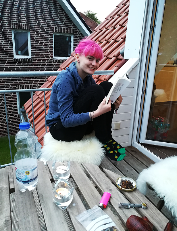 Lucia sitzt mit angewinkelten Beinen auf einem Stuhl auf dem Balkon unserer Ferienwohnung und liest Geschichten aus einem Buch vor. Vor ihr steht der Balkontisch mit Annas Pfeife, einem Feuerzeug und Kerzen darauf.