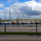 Mehrere Schiffe in einer Reihe im Hafen von Neßmersiel bei sonnigem Wetter.