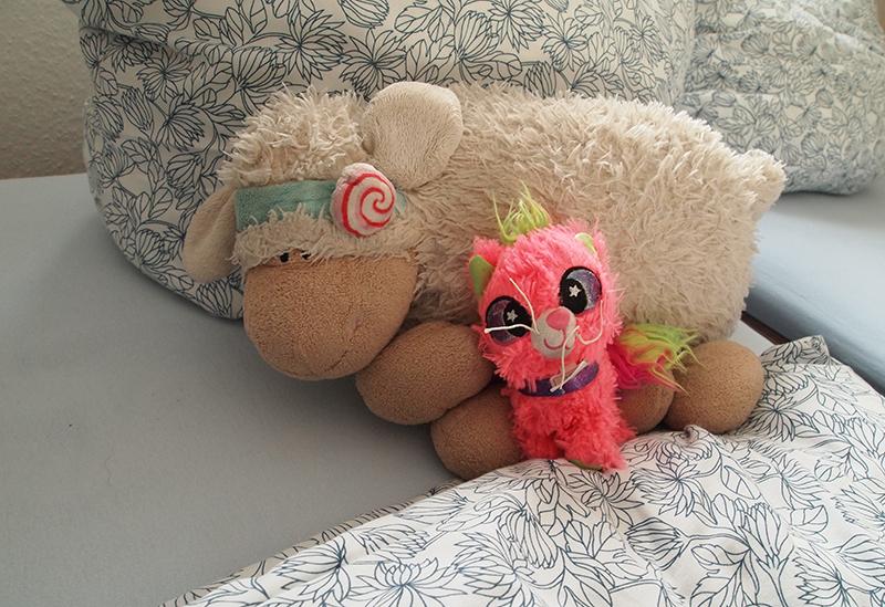 Ein Plüschschaf (Plattschaf) und eine kleine rosa Plüschkatze (Punkycat) auf dem Kopfkissen unseres Bettes.