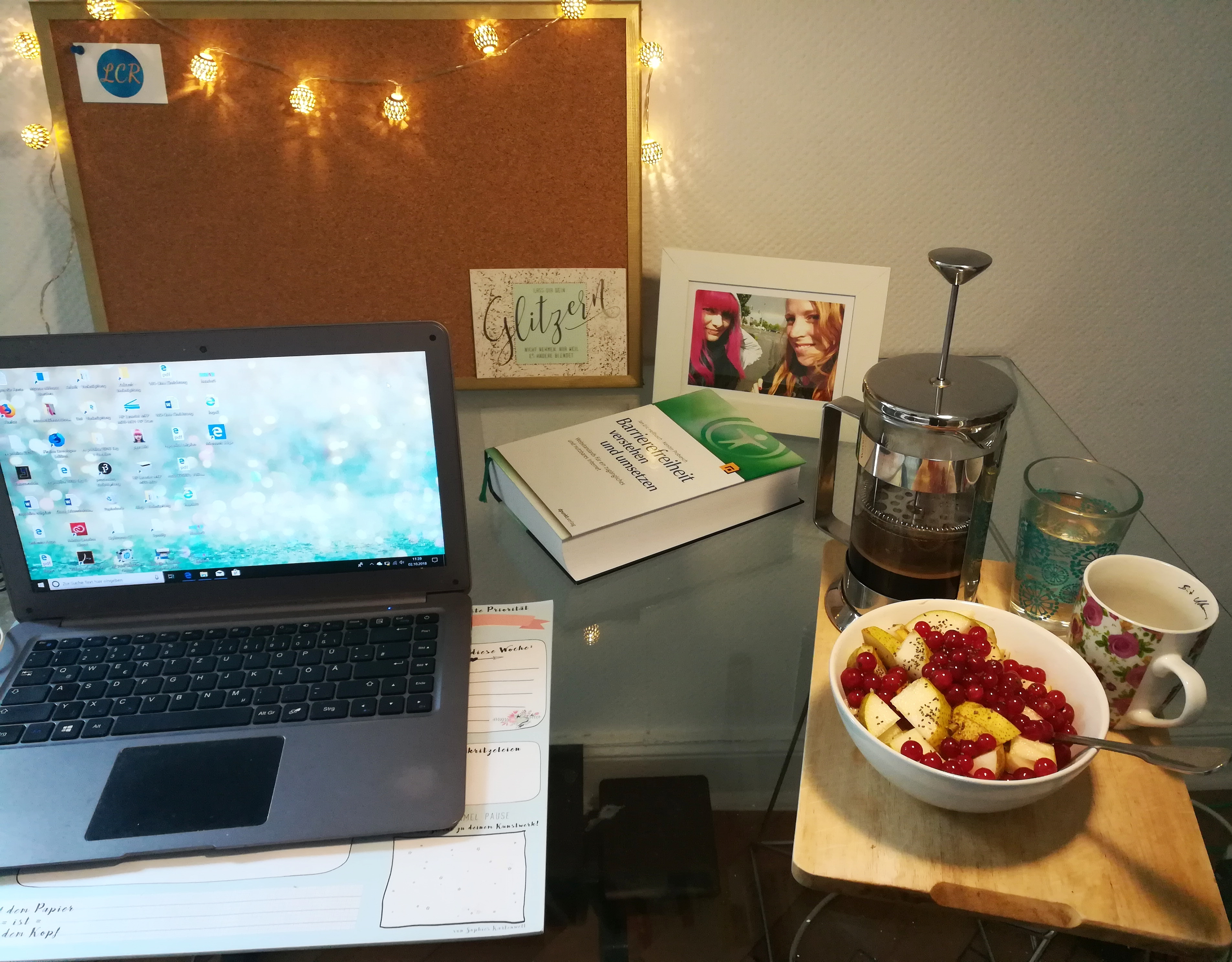 Schreibtisch mit Laptop und Frühstück (Kaffeekanne, Haferbrei mit Apfel und Johannisbeeren).