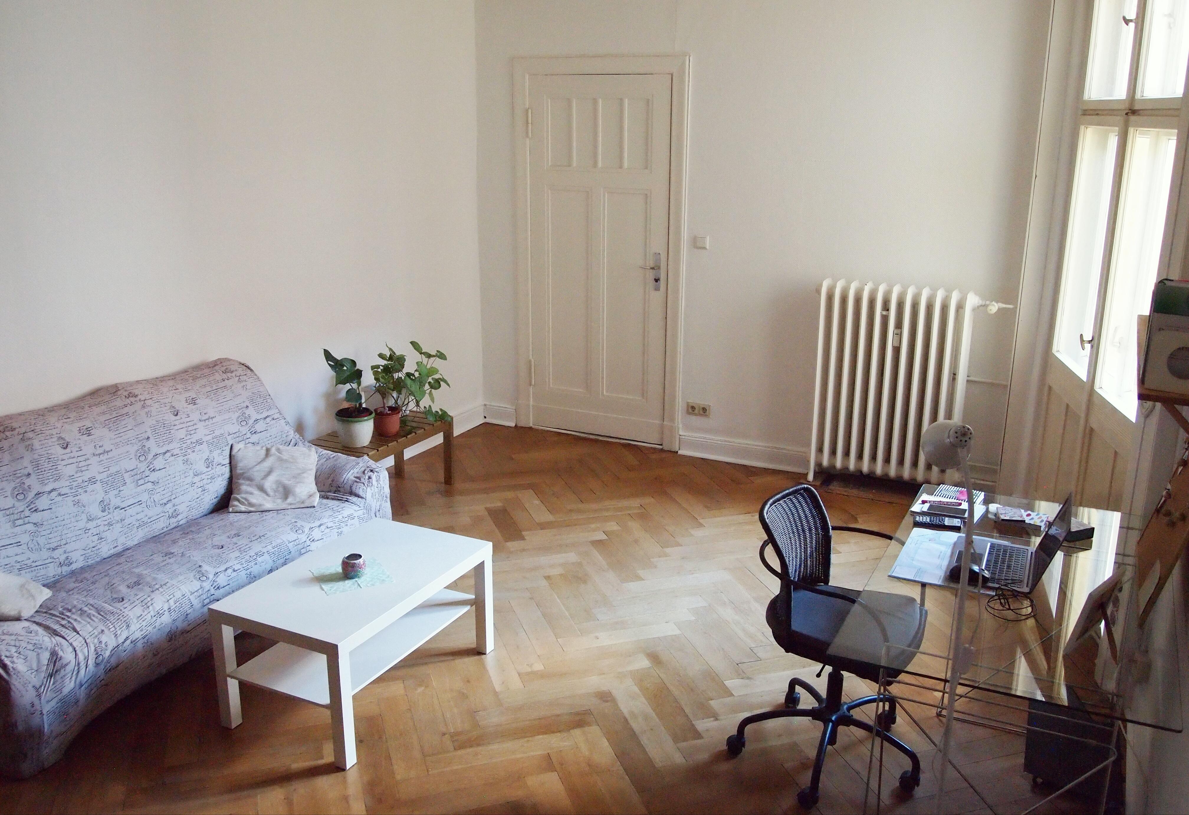 Wohnzimmer mit cremefarbenem Vintage-Sofa, weißem Couchtisch, Schreibtisch aus Glas und schwarzem Schreibtischstuhl mit Korblehne.